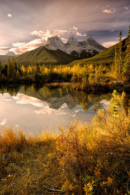 The Three Sisters reflected in the lake near Canmore, Alberta, Canada